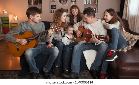 Portrait of a happy large family, children and parents sing and play the guitar together, indoor