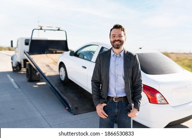 Portrait of a happy latin guy smiling because the tow truck service came to get his broken-down car from the side of the road