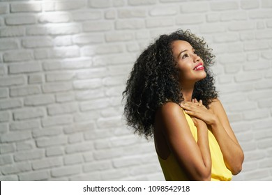 Portrait of happy latina woman smiling and saying prayer. Black girl looking up while praying.