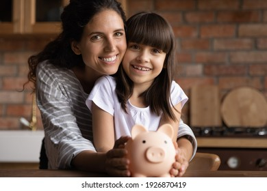 Portrait of happy Latino young mom and small 8s daughter recommend smart living and saving. Smiling Hispanic mother and little teen girl child hold piggybank feel economical making investment.