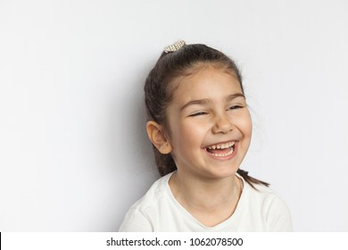 Portrait of a happy laughing child girl on white background