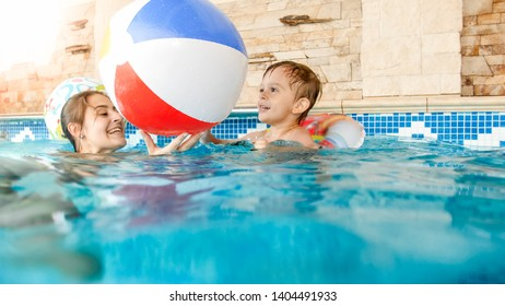 Portrait of happy laughing toddler boy with mother playing with colorful inflatable beach ball in swimming pool at summer hotel resort