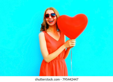 Portrait happy laughing woman in red dress, a balloon in the shape of a heart on blue background