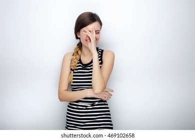 Portrait of happy laughing young beautiful woman in striped shirt doing facepalm posing for model tests against studio background