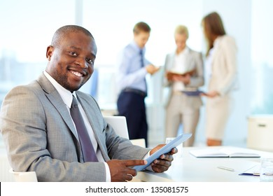 Portrait of happy leader with touchpad looking at camera in working environment