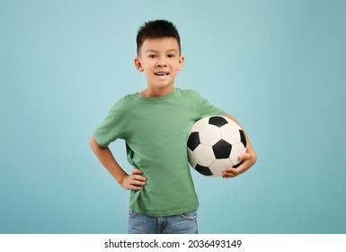 Portrait Of Happy Little Asian Boy Posing With Football Ball In Hand Over Blue Studio Background, Small Korean Male Child Enjoying Playing Soccer, Looking At Camera And Smiling, Copy Space