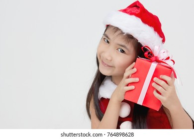Portrait of happy little Asian girl in red Santa dress holding present on isolated