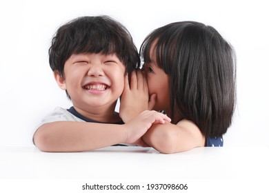 Portrait of happy little Asian siblings sharing secrets against white background.