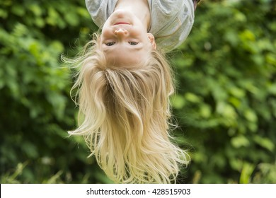 Portrait of Happy little blond girl playing on a rope web playground outdoor. Upside down