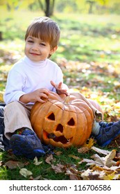 Portrait of a happy little boy in the autumn wood with Halloween pumpkin