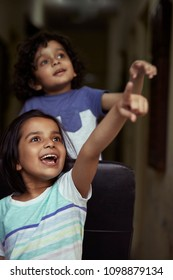 Portrait of happy little boy and a girl pointing towards sky