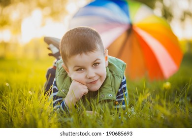 Portrait of a happy little boy in the green park