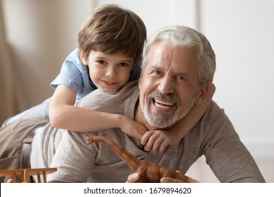 Portrait of happy little boy hug cuddle with overjoyed mature grandfather playing at home together, smiling small preschooler grandchild posing look at camera embracing smiling senior grandparent