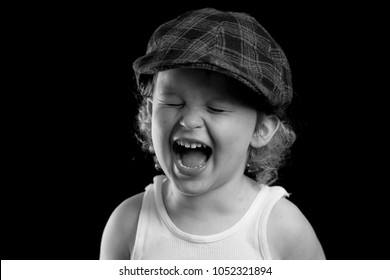 A portrait of a happy little boy laughing and smiling. He is wearing a white tank top and a plaid hat. The black and white headshot is of a child model and a child actor. The boy is playful, smiley.