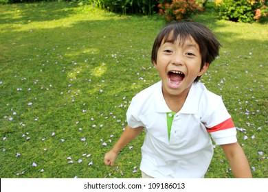 Portrait of happy little boy running in the park