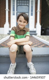 Portrait of happy little boy sitting on front steps of house