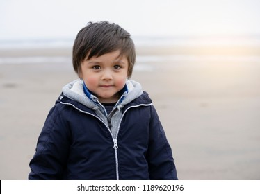Portrait happy little boy with warm clothes standing on the beach with blurry background by the sea,Active 4-5 years old kid smiling with sand on his face wearing hoodie playing on the beach in Autumn