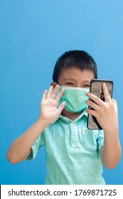 portrait of happy little boy wearing mask gesturing hi hello with his right hand to mobile phone.child communicating with other family member on video call. isolated with blue background