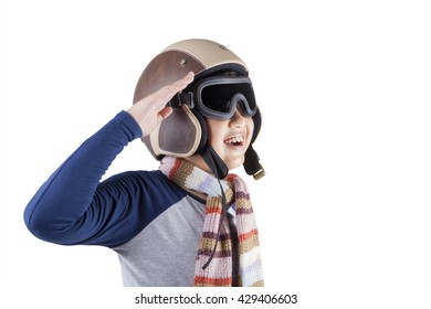 Portrait of happy little boy wearing an aviator helmet while giving a respectful hand gesture