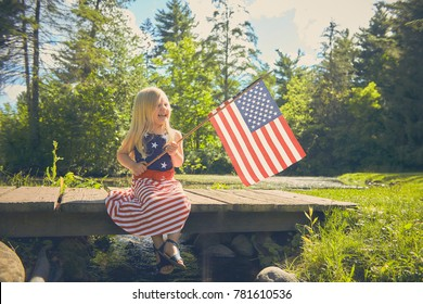 Portrait of happy little Caucasian girl wearing dress with stars and stripes sitting on wooden bridge waving American flag at Independence day