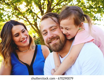 Portrait of happy little daughter embracing her bearded father. Mother looking at them and smiling. Happy parents in summer