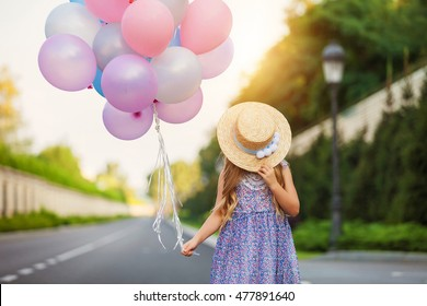Portrait of a happy little girl with balloons. Vintage concept