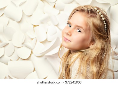 Portrait of a happy little girl with beautiful blonde hair posing by a background of white paper flowers. Kids fashion. Cosmetics, accessories.