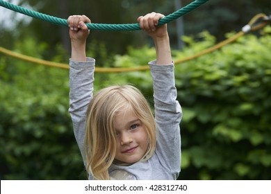 Portrait of Happy little girl climbing on a rope playground outdoor