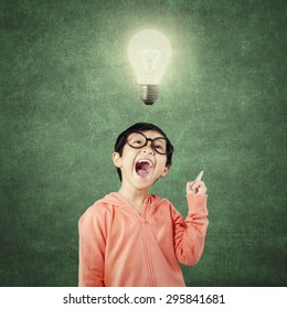 Portrait of happy little girl gets idea in the classroom under a bright light bulb
