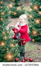 Portrait of happy little girl hanging baubles on tree at farm. Cute girl wearing red coat and scarf standing among Christmas trees outdoors