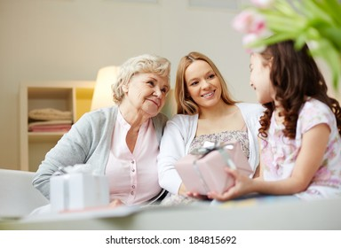 Portrait of happy little girl, her mother and grandmother with giftboxes talking at home