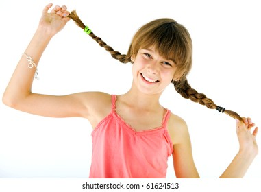 Portrait of happy little girl holding her braids, smiling at camera, isolated on white