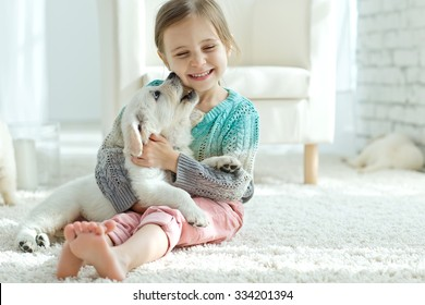 Portrait of happy little girl at home with labrador puppy
