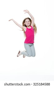 Portrait of a happy little girl jumping in the air against a white background.