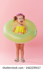 Portrait of happy little girl with neon inflatable rubber circle having fun isolated on pink background