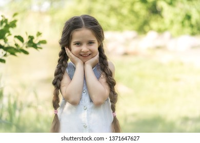 Portrait of a happy little girl on nature background.