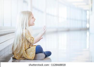 Portrait of happy little girl sitting on floor indoors