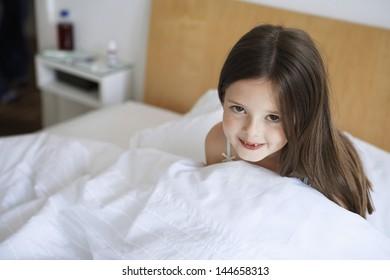 Portrait of happy little girl sitting in bed
