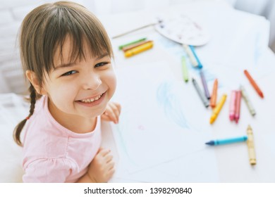 Portrait of happy little girl smiling and drawing with colorful pencils, dressed in pink t-shirt. Pretty preschooler child painting and learning at kindergarten. People, childhood, education