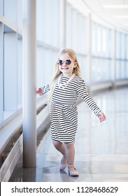 Portrait of happy little girl in striped dress and sunglasses