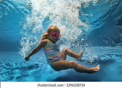 Portrait of a happy little girl in swimming pool