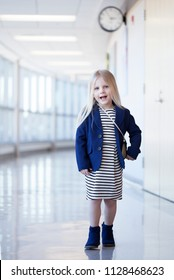 Portrait of happy little girl wearing dress and blue jacket