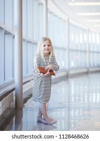 Portrait of happy little girl wearing striped dress with wallet