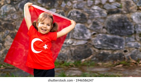 Portrait of happy little kid. Cute baby with Turkish flag t-shirt. Toddler hold Turkish flag in hand. Patriotic holiday. Adorable child celebrates national holidays. Copy space for text. - Shutterstock ID 1946586247