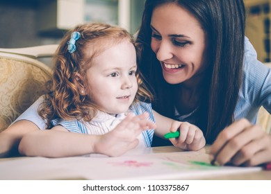 Portrait of happy little redhead girl sitting at table and drawing with her mother or nanny. Young woman looking at daughter and smiling