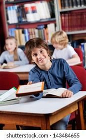 Portrait of happy little schoolboy giving book while sitting at table in library with classmates in background