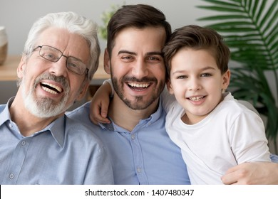 Portrait of happy little son, father and grandfather sit on couch hugging posing for family picture together, smiling three generations of men embrace look at camera laughing rest on sofa at home