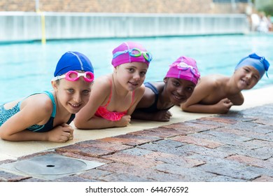 Portrait of happy little swimmers leaning at poolside