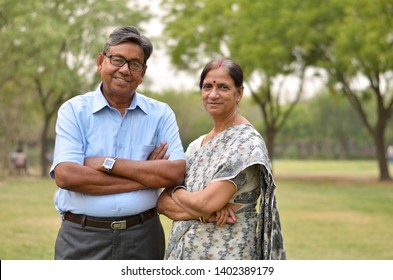Portrait of a happy looking retired senior Indian man and woman couple smiling and posing with hands crossed in a park outdoor during spring/summer season in Delhi, India. Concept love