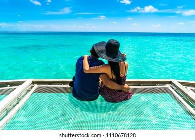 Portrait of happy loving couple at beautiful water villa at Maldives island. Travel and Vacation. Outdoor shot